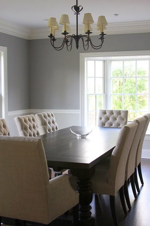 Gray dining room walls are offset by white wainscoting and cream furniture