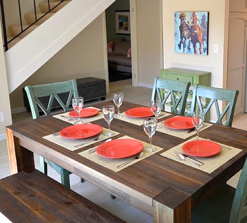 Open dining room painted beige with red and green colorful accessories