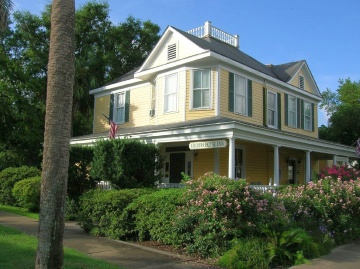 House exterior painted in a yellow and green color scheme
