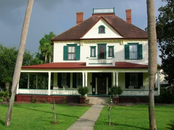 Brick house painted white, green and red