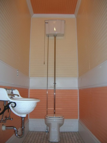Powder room ceiling and walls painted in different shades of orange
