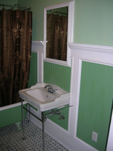 Bathroom painted with different shades of green and decorated with brown