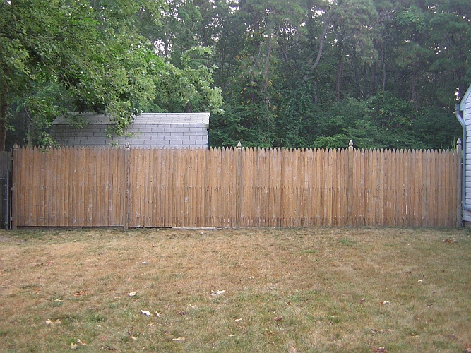 Before: bare wood fence