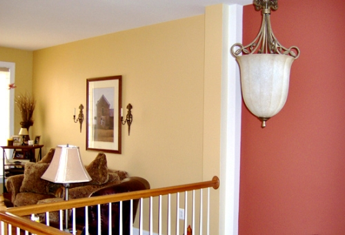 Bright yellow living room wall color is juxtaposed with the bold red foyer