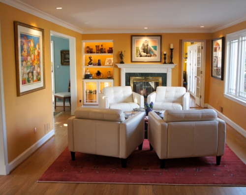 Warm, yellow-orange wall color connects the living room decor