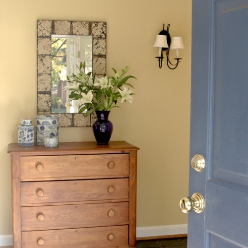 Soft yellow paint color on the wall complemented by a blue door