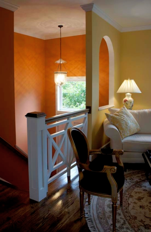Bold orange foyer wall color contrasts with the sunny yellow living room