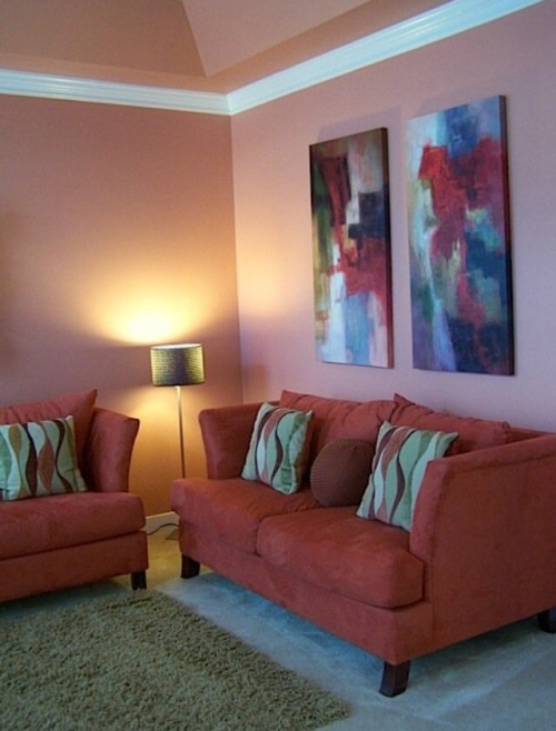 Salmon colored painted walls with green and orange accents and furniture
