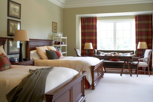 Green bedroom walls are offset by red plaid decor elements