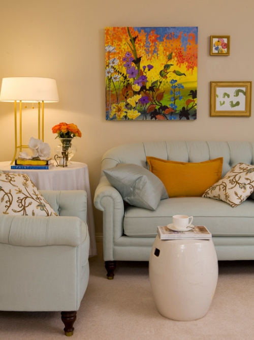 Beige living room walls with french blue furniture and bright wall art