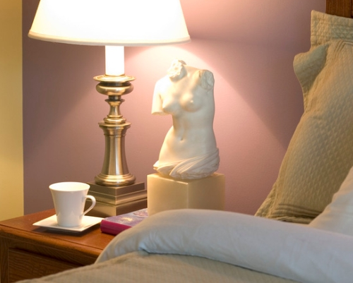 Rose purple accent wall in a bedroom painted a golden yellow color