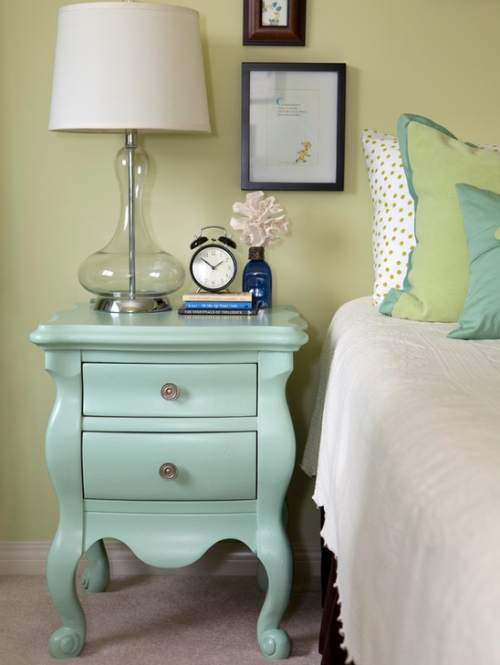 Bedroom walls painted green with turquoise and off-white decor accents
