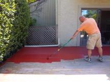 Alek is applying deck stain