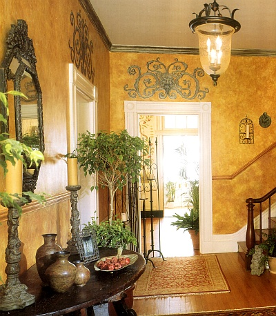 Sponged off foyer walls in shades of gold, decorated with stencil designs