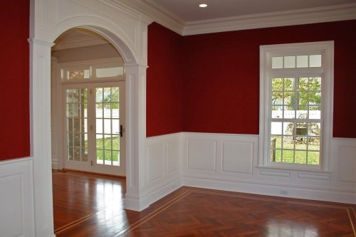 Dining room walls painted a deep red above the wainscoting