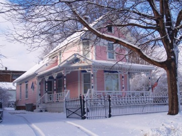 Pink and white Victorian house in winter snow