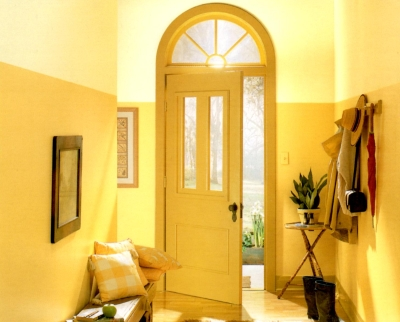 Deep yellow front door in a hallway painted in different shades of the same hue