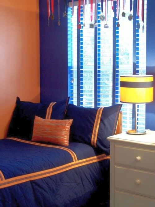 Teenage boy's orange bedroom with a deep royal blue accent wall