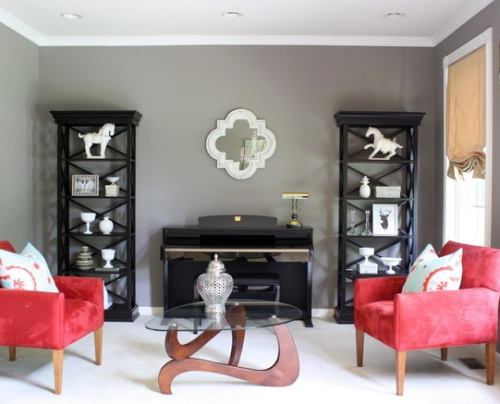 Gray living room walls are offset by the black shelves and red chairs
