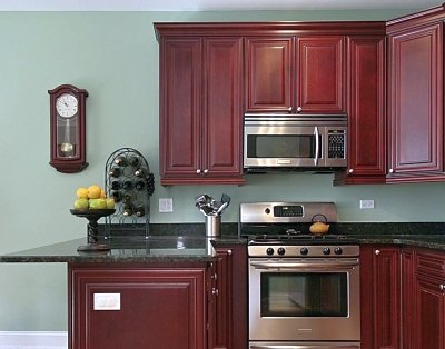 Red stained kitchen cabinets with sage green walls
